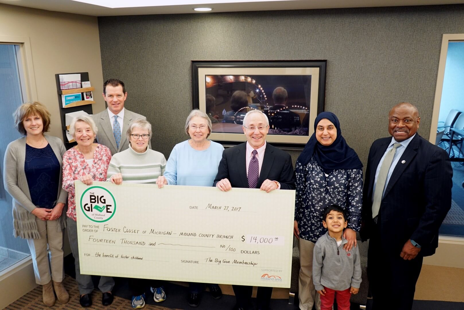 Members of The Big Give pose with a check for Foster Closet of Michigan